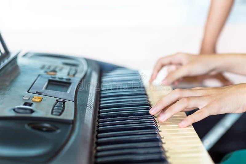 Ciérrese encima de la vista lateral de las manos de la mujer que juegan el piano con la mano del fondo borroso del instructor imagen de archivo libre de regalías