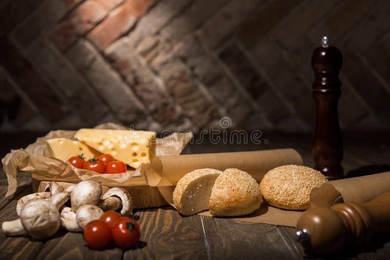 ciérrese encima de la vista de los tomates de cereza, del queso, de las setas y de los panes del pan frescos en el papel de la ho imágenes de archivo libres de regalías