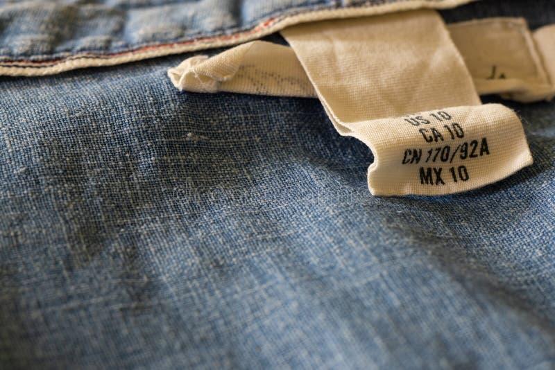 Ciérrese encima de la vista macra de la ropa femenina de la talla de camisa de los tejanos foto de archivo libre de regalías