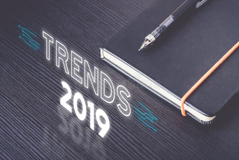 Ciérrese encima de la vista superior de las tendencias 2019 con el cuaderno negro con el lápiz mecánico moderno en la tabla de ma fotografía de archivo