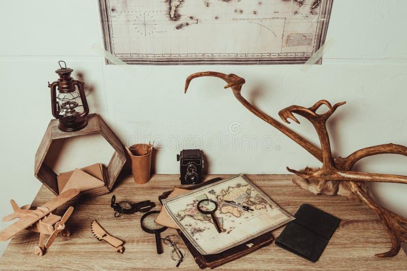 ciérrese encima de la vista de la tabla con el mapa, lentes, lupas, cámara retra de la foto foto de archivo