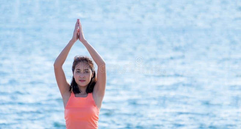 Ciérrese encima de la yoga principal femenina que hace actitud de la trenza en la playa y s azul fotografía de archivo libre de regalías