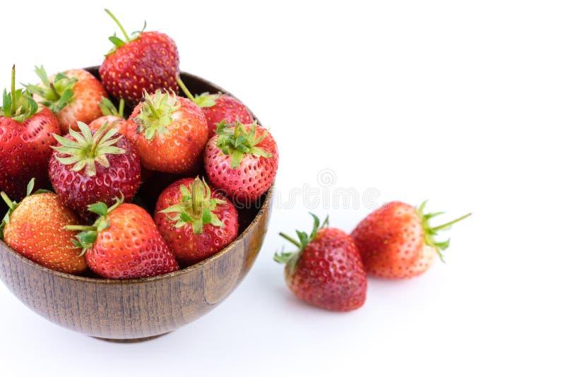 Ciérrese encima de las frutas frescas de las fresas en un cuenco de madera aislado en el fondo blanco fruta y concepto sano fotos de archivo