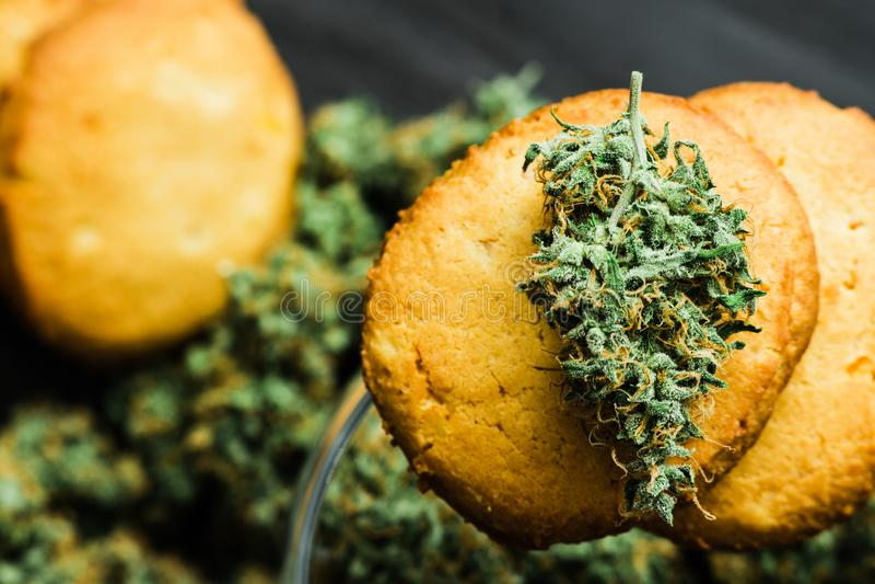 Ciérrese encima de las galletas macras con los cáñamos y los brotes de la marijuana en la tabla utilice CBD foto de archivo