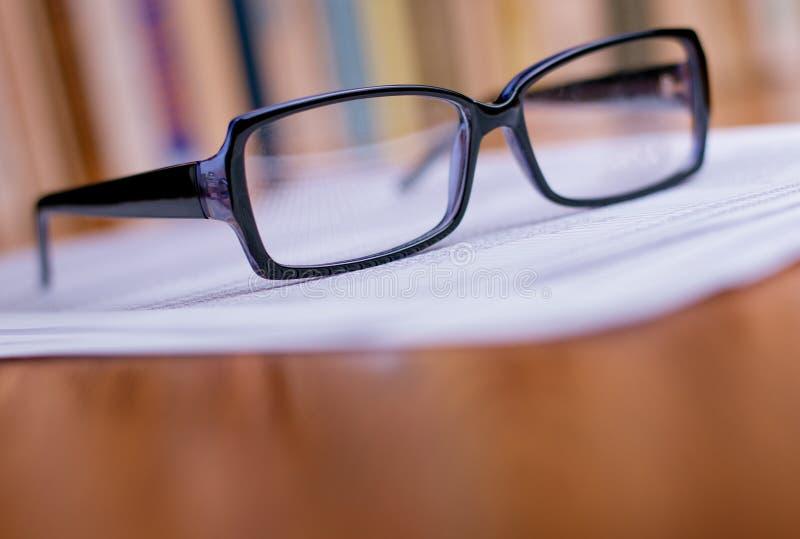 Ciérrese encima de las lentes encima de los Libros Blanco fotos de archivo