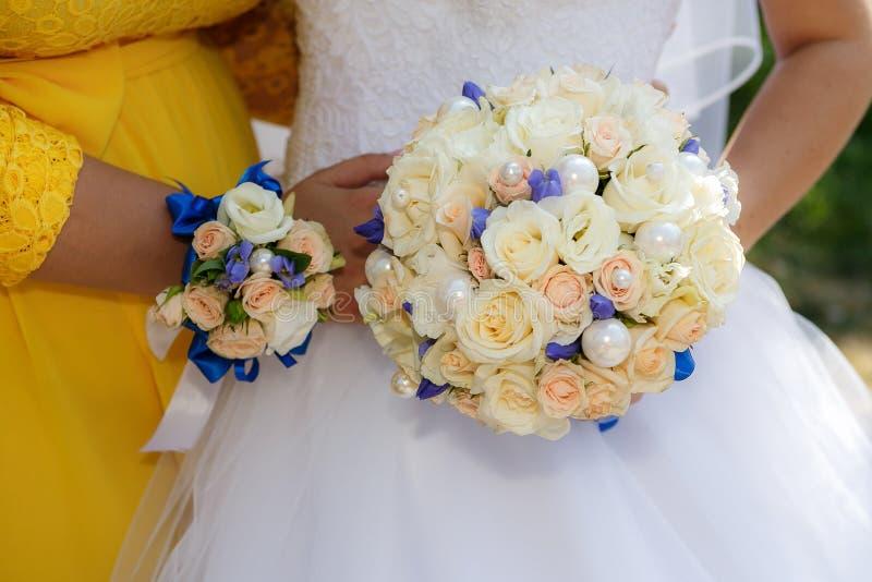 Ciérrese encima de las manos con el bride& x27; s y bridesmaid& x27; ramo de s foto de archivo