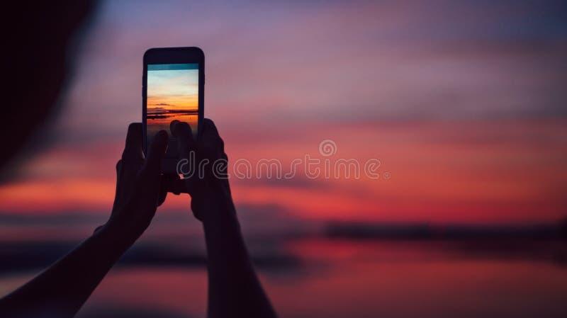 Ciérrese encima de las manos con la imagen del smartphine de la hembra que hace una puesta del sol increíble el tiro rápido fotografía de archivo libre de regalías
