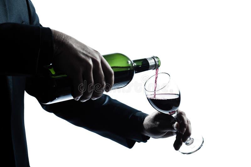 Ciérrese encima de las manos del hombre que vierten el vino rojo en un vidrio fotografía de archivo libre de regalías
