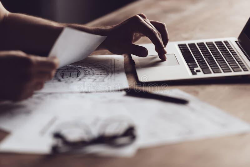 Ciérrese encima de las manos del hombre usando el ordenador portátil en la tabla de madera imagenes de archivo
