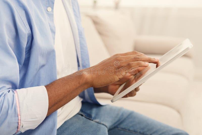 Ciérrese encima de las manos del hombre usando la tableta digital fotografía de archivo libre de regalías