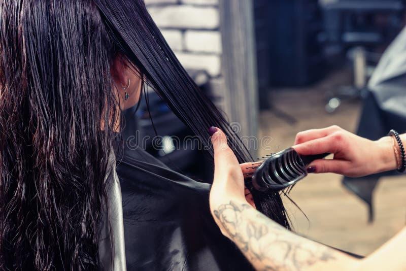 Ciérrese encima de las manos del peluquero profesional de sexo femenino que peina la ha mojada imágenes de archivo libres de regalías