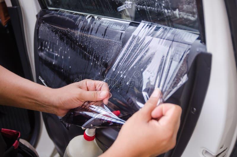 Ciérrese encima de las manos del tiro del hombre que quitan el viejo foco de la película de la ventanilla del coche encendido imágenes de archivo libres de regalías