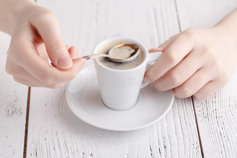Ciérrese encima de las manos femeninas con la taza de café en la tabla Primer del descanso para tomar café fotos de archivo libres de regalías