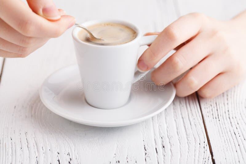 Ciérrese encima de las manos femeninas con la taza de café en la tabla Primer del descanso para tomar café foto de archivo
