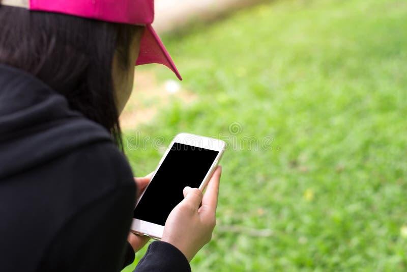 Ciérrese encima de las manos femeninas que sostienen la pantalla elegante del negro del teléfono para la copia imagenes de archivo