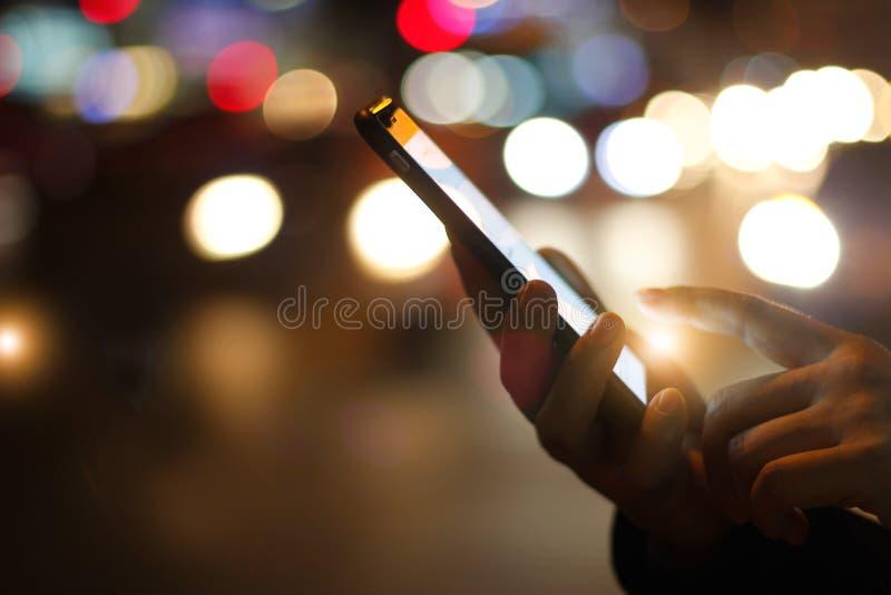 Ciérrese encima de las manos femeninas usando smartphone móvil en cuesta iluminada imágenes de archivo libres de regalías