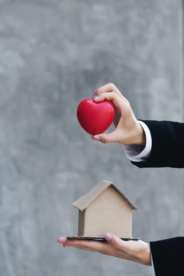 Ciérrese encima de las manos de la casa de la tenencia del agente inmobiliario con el corazón Concepto 6 de las propiedades inmob imágenes de archivo libres de regalías