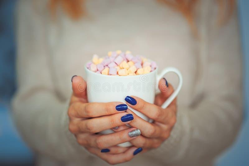 Ciérrese encima de las manos de la hembra de la mujer joven con la manicura que sostiene una taza de cacao caliente con la ventan imagen de archivo