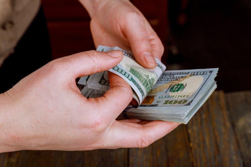 ciérrese encima de las manos de la mujer que cuentan cuentas de dólar de EE. UU. imágenes de archivo libres de regalías