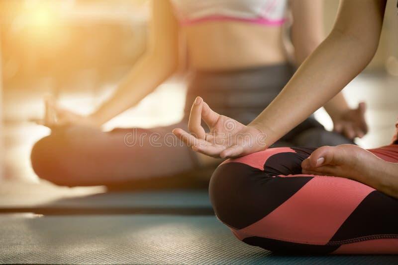 Ciérrese encima de las manos de la mujer que hacen la yoga que ejercita la meditación el grupo de muchacha medita asistir en la p imagen de archivo