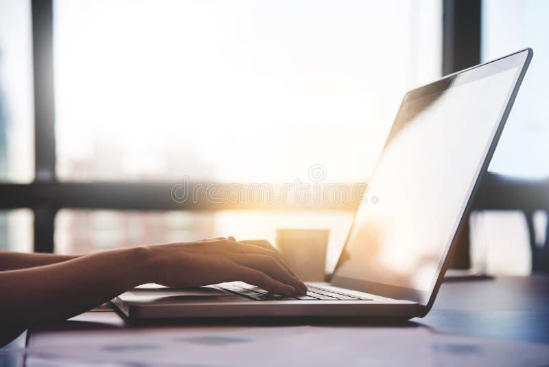 Ciérrese encima de las manos de la mujer usando el ordenador portátil para su trabajo imagen de archivo libre de regalías