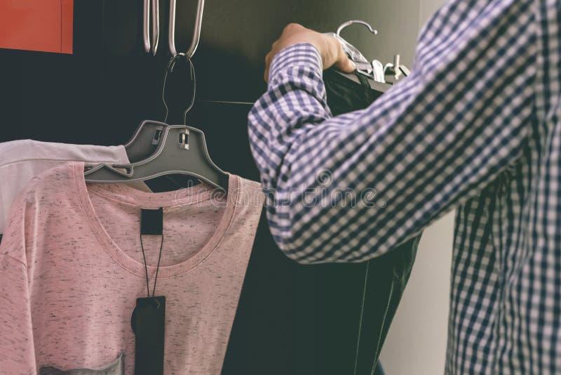 Ciérrese encima de las manos de la persona que intentan la selección y elegir de la ropa casual en vestuario de las compras foto de archivo