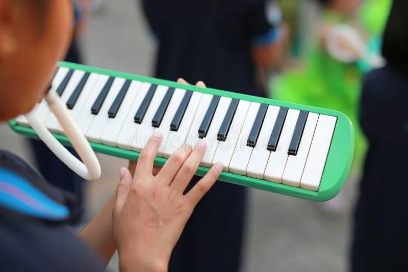Ciérrese encima de las manos de los estudiantes que juegan a la banda melodian la música que usted aprendió en escuela secundaria foto de archivo