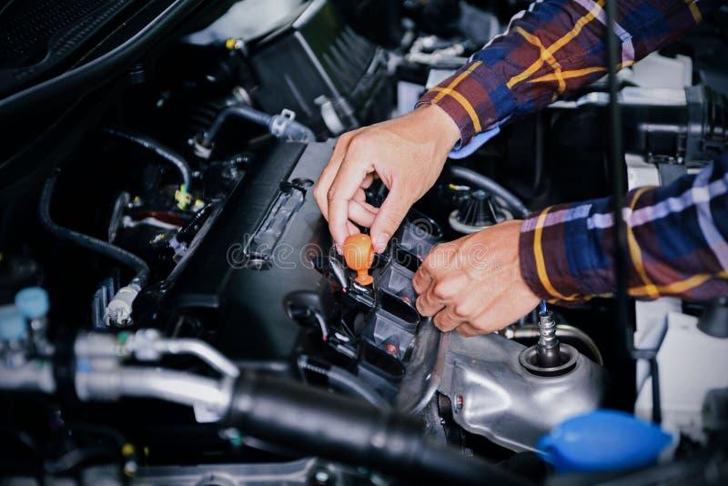 Ciérrese encima de las manos que comprueban el nivel de aceite de lubricante de motor de coche de profundo-s imagenes de archivo