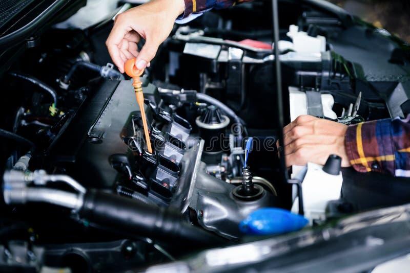 Ciérrese encima de las manos que comprueban el nivel de aceite de lubricante de motor de coche de profundo-s imagen de archivo