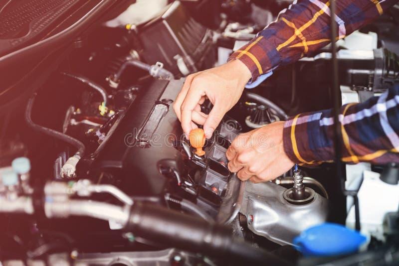 Ciérrese encima de las manos que comprueban el nivel de aceite de lubricante de motor de coche de profundo-s fotografía de archivo