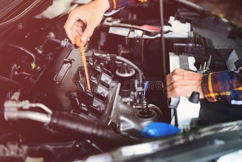 Ciérrese encima de las manos que comprueban el nivel de aceite de lubricante de motor de coche de profundo-s fotos de archivo