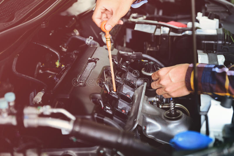 Ciérrese encima de las manos que comprueban el nivel de aceite de lubricante de motor de coche de profundo-s foto de archivo