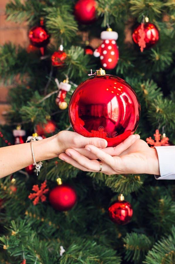 Ciérrese encima de las manos que sostienen la bola de la Navidad en fondo del árbol de Navidad imagen de archivo libre de regalías