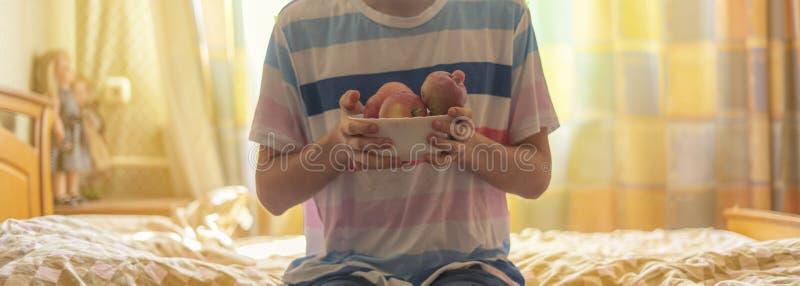 Ciérrese encima de las manos que sostienen una placa con las manzanas crudas frescas de la fruta en cama por la mañana f fotografía de archivo libre de regalías