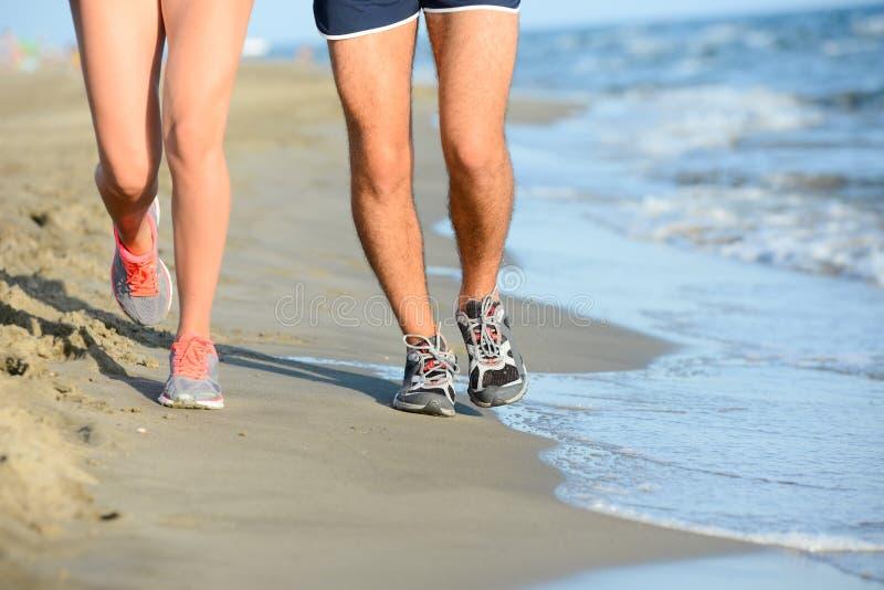 Ciérrese encima de las piernas del hombre joven y de la mujer de los pares que corren en la arena en la orilla de la playa por el fotografía de archivo