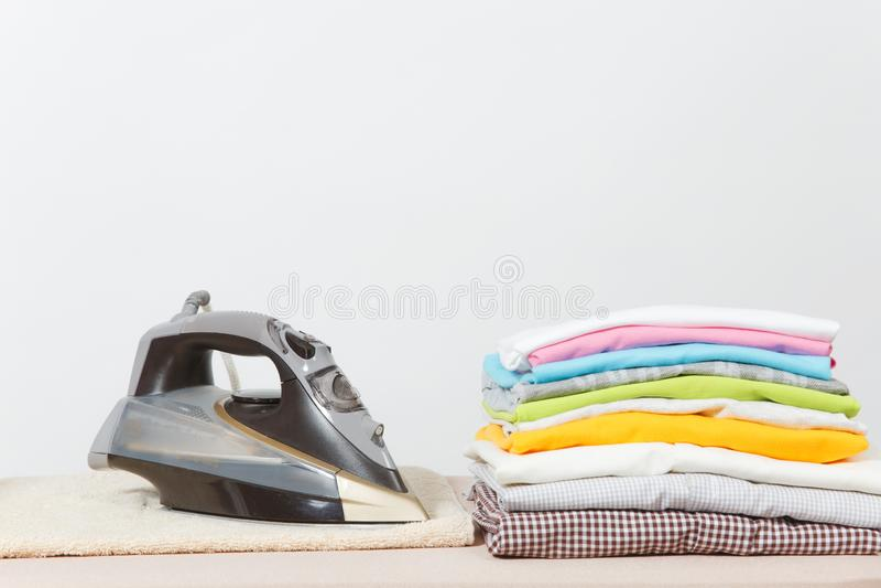 Ciérrese encima de lavadero lavado ropa colorida del hierro de vapor en el fondo blanco housekeeping Copie el anuncio del espacio imagen de archivo