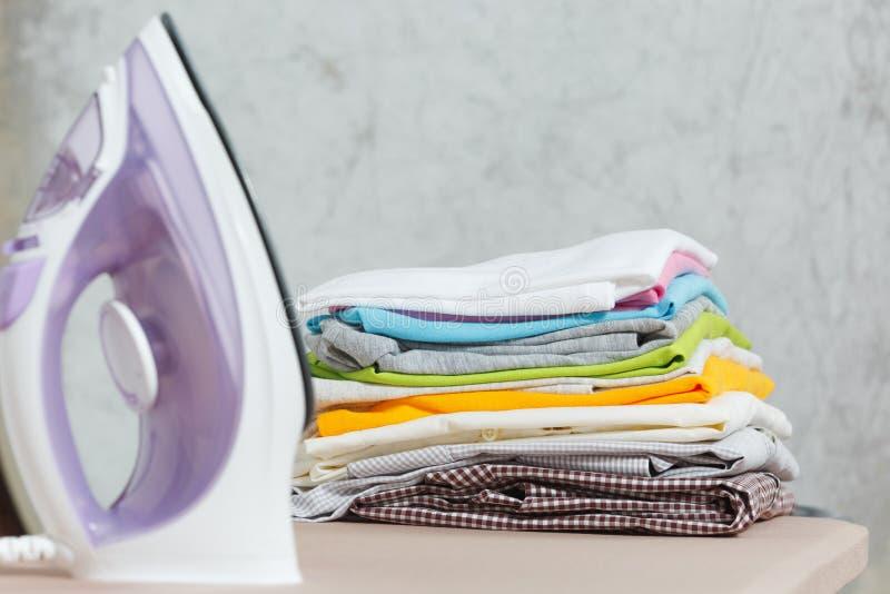 Ciérrese encima de lavadero lavado ropa colorida del hierro de vapor en el fondo blanco housekeeping Copie el anuncio del espacio imagenes de archivo