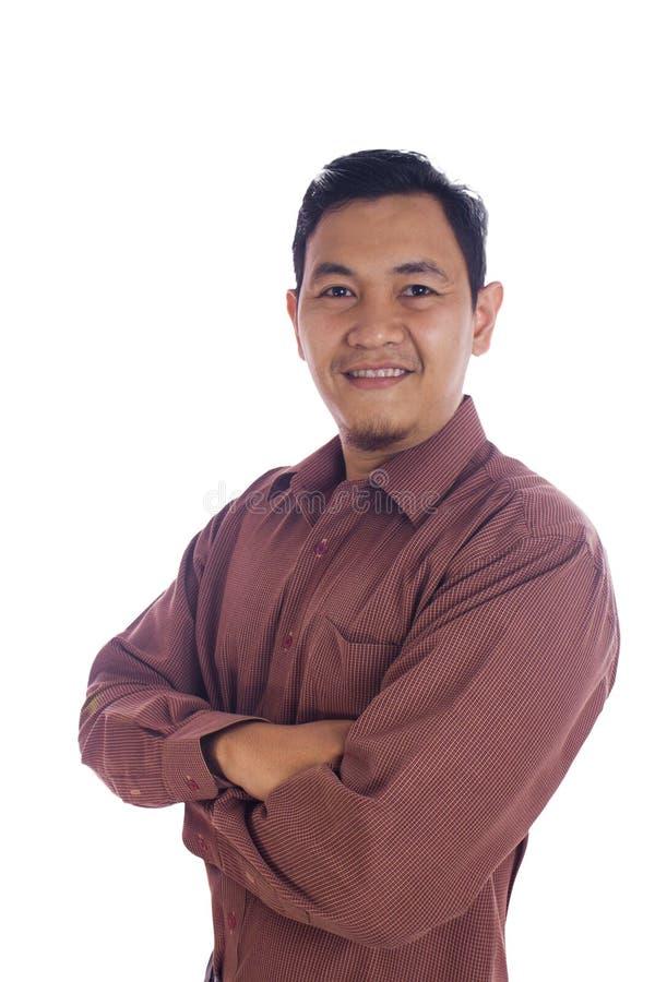 Ciérrese encima de los brazos cruzados sonrientes del hombre asiático foto de archivo