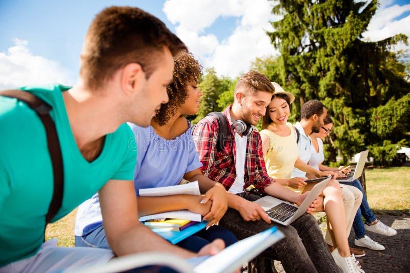 Ciérrese encima de los compañeros de clase alegres cosechados del od seis del tiro, sentándose en un b fotos de archivo libres de regalías