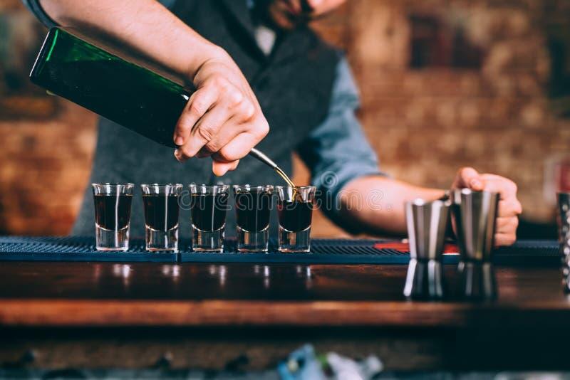 Ciérrese encima de los detalles del camarero que sirven bebidas alcohólicas en el partido fotografía de archivo libre de regalías