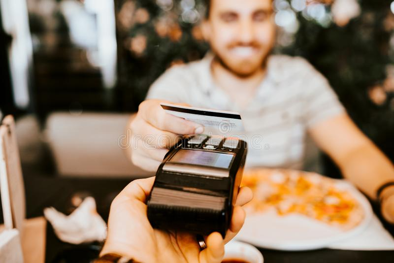 Ciérrese encima de los detalles del pago con tarjeta de crédito de los contactelss en el restaurante fotos de archivo libres de regalías