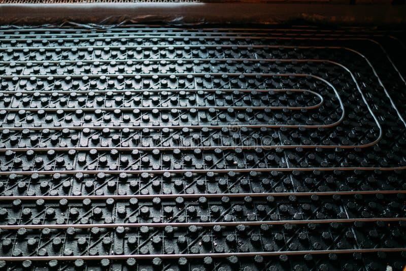 Ciérrese encima de los detalles de la calefacción de piso, detalles debajo del piso de la instalación de calefacción industrial imagenes de archivo