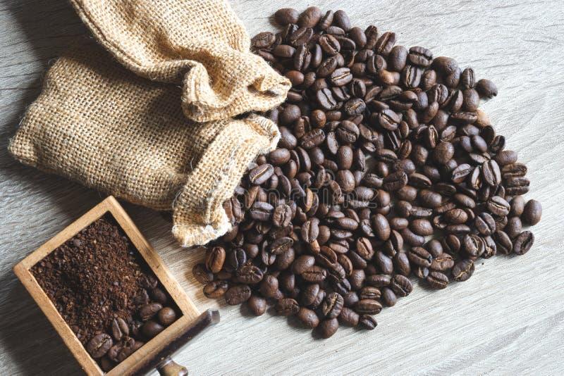 Ciérrese encima de los granos de café asados con el pequeño saco y la haba machacada imagen de archivo libre de regalías