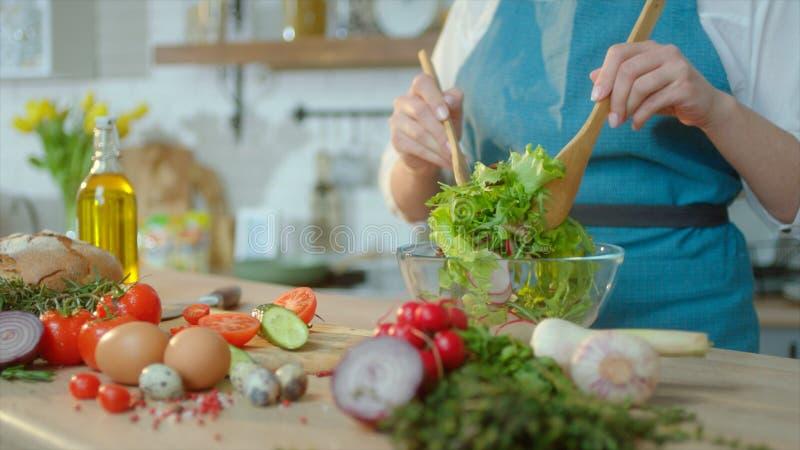 Ciérrese encima de los ingredientes frescos están en la tabla que corta Las manos femeninas están cocinando la ensalada fresca en fotos de archivo
