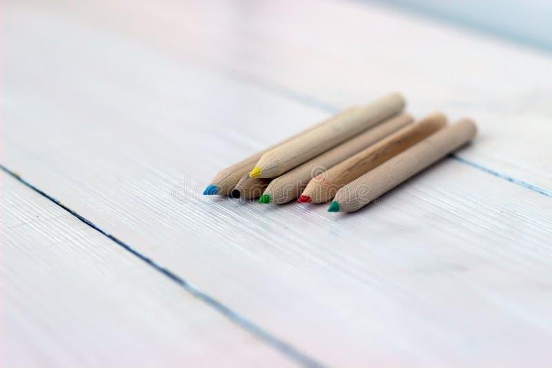 Ciérrese encima de los lápices del color en la tabla de madera, del concepto de arte y de la educación imagen de archivo libre de regalías