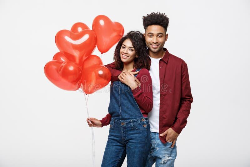 Ciérrese encima de los pares afroamericanos atractivos huging y que sostienen el globo rojo del corazón imagen de archivo libre de regalías
