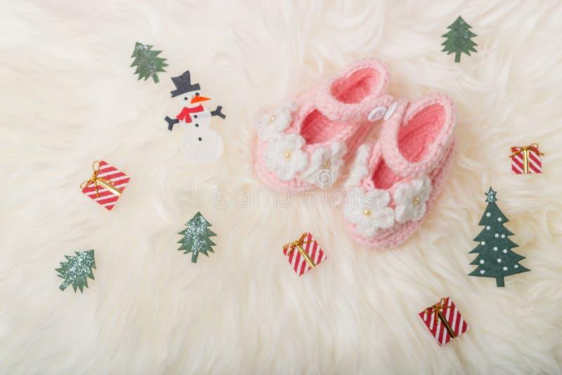 Ciérrese encima de los zapatos hechos punto bebé en el fondo combinado blanco Feliz Navidad y tarjeta de felicitación de la Feliz imagen de archivo