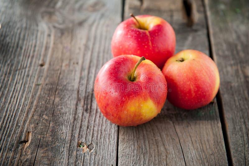 Ciérrese encima de manzanas rojas orgánicas maduras frescas con descensos del agua en la tabla de madera rústica Espacio para el  fotografía de archivo