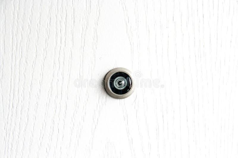 Ciérrese encima de mirilla de la lente de la puerta en la textura de madera blanca foto de archivo libre de regalías
