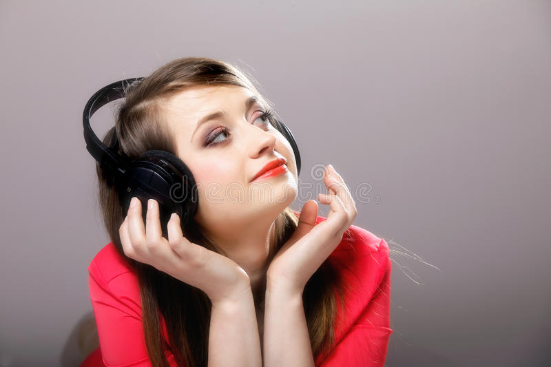Ciérrese encima de muchacha sonriente con los auriculares imagen de archivo libre de regalías